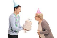 拿着与一个成熟妇女吹的Th的年轻人生日蛋糕 免版税图库摄影