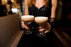 拿着与一个酒精鸡尾酒的女孩两块玻璃变酸混合 库存照片