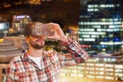 拿着与一个轻的城市的偶然人人的综合图象真正玻璃在背景中 库存图片