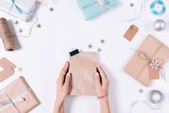拿着与一件礼物的女性手一个包裹在圣诞节装饰中 免版税库存图片