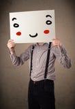 拿着与一张兴高采烈的面孔的商人纸板对此 免版税库存照片