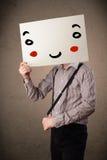 拿着与一张兴高采烈的面孔的商人纸板对此 库存照片