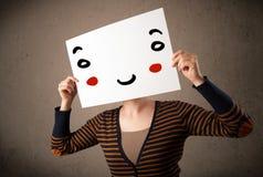 拿着与一张兴高采烈的面孔的妇女纸板对此 图库摄影