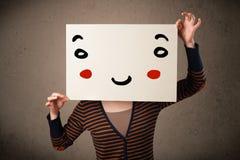拿着与一张兴高采烈的面孔的妇女纸板对此 免版税库存照片
