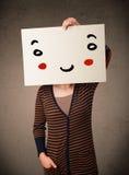 拿着与一张兴高采烈的面孔的妇女纸板对此 库存照片