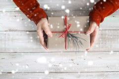 拿着与一条红色丝带的圣诞节礼物和雪的一件红色毛线衣的一名妇女在一张木桌上 库存照片