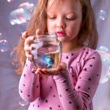 拿着与一条蓝色鱼的小女婴一fishbowl 关心conce 免版税库存图片