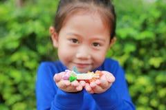 拿着与五颜六色包装纸的亚裔儿童女孩一些泰国糖和果子奶糖在她的手上 在糖果的焦点在她的手上 免版税库存图片