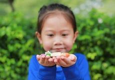 拿着与五颜六色包装纸的亚裔儿童女孩一些泰国糖和果子奶糖在她的手上 在糖果的焦点在她的手上 库存图片