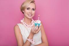 拿着与五颜六色的蜡烛的美丽的少妇小蛋糕 生日,假日 免版税库存图片