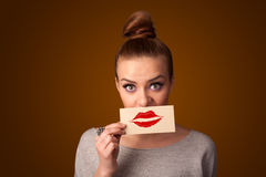 拿着与亲吻唇膏标记的愉快的俏丽的妇女卡片 免版税图库摄影