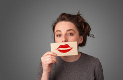 拿着与亲吻唇膏标记的愉快的俏丽的妇女卡片 免版税库存图片