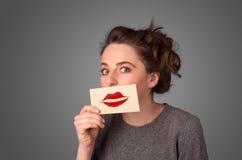 拿着与亲吻唇膏标记的愉快的俏丽的妇女卡片 库存图片