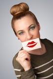 拿着与亲吻唇膏标记的愉快的俏丽的妇女卡片 免版税库存照片