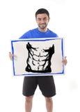 拿着与健身房健身俱乐部六块肌肉腹部凹道广告行销的体育人广告牌  库存照片