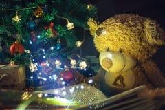 拿着与光的玩具熊一本开放书 读书圣诞节传说 除夕魔术的概念 免版税库存图片