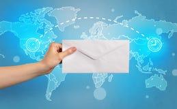 拿着与全球性概念的手信封 库存照片