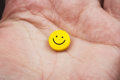 拿着与兴高采烈的面孔的手的接近的看法一个黄色药片对此 库存图片