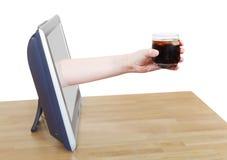 拿着与冰的手可乐在玻璃倾斜电视 库存照片