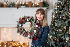 拿着与冷杉的少妇圣诞节花圈在假日分支 庆祝新年度 在背景  免版税图库摄影