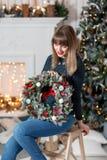 拿着与冷杉的少妇圣诞节花圈在假日分支 庆祝新年度 在背景  免版税库存图片