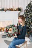 拿着与冷杉的少妇圣诞节花圈在假日分支 庆祝新年度 在背景  图库摄影