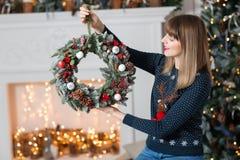 拿着与冷杉的少妇圣诞节花圈在假日分支 庆祝新年度 在背景  库存照片