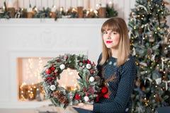 拿着与冷杉的少妇圣诞节花圈在假日分支 庆祝新年度 在背景  免版税库存照片