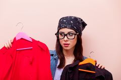 拿着与凝块的班丹纳花绸的年轻红头发人女孩设计师挂衣架 免版税库存图片