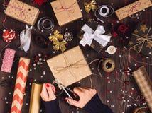 拿着与剪刀的妇女手麻线绳索切开的和包装的圣诞节礼物盒的 免版税库存照片