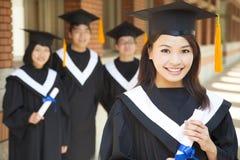 拿着与同学的美丽的大学毕业生文凭 免版税库存图片