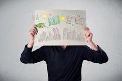 拿着与图和都市风景的商人一张纸在前面o 库存图片