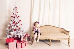 拿着与圣诞树的微笑的孩子女孩白色玩具熊户内 童年 免版税库存图片