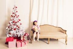 拿着与圣诞树的微笑的孩子女孩白色玩具熊户内 童年 免版税库存照片