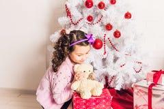 拿着与圣诞树的微笑的孩子女孩白色玩具熊户内 童年 免版税图库摄影