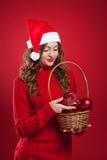 拿着与圣诞树装饰的美丽的女孩篮子 免版税库存图片