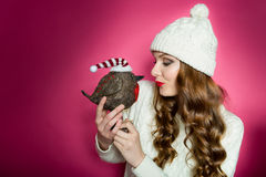 拿着与圣诞老人帽子的华美的妇女一只逗人喜爱的玩具鸟 库存照片