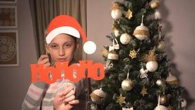 拿着与圣诞老人` s属性的女孩横幅 免版税库存照片