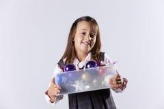 拿着与圣诞节球的小女孩一个配件箱 库存照片