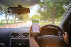 拿着与地图gps航海应用的女性司机手汽车指点盘区在高速公路 库存图片