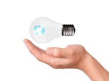 拿着与地球行星的手电灯泡 免版税图库摄影