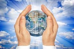 拿着与基督徒十字架的手行星地球。 免版税库存图片
