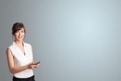 拿着与复制空间的可爱的妇女一个电话 库存照片