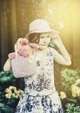 拿着与复活节兔子的小女孩一个手袋-减速火箭 免版税库存图片
