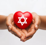 拿着与大卫王之星的女性手心脏 免版税图库摄影