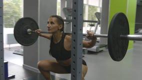 拿着与大量的重量的少妇杠铃在她的肩膀,她蹲 在健身房的强的女孩训练 影视素材