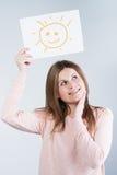 拿着与太阳的妇女纸板 库存照片
