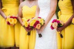 拿着与女傧相的新娘花束在背景中 库存图片