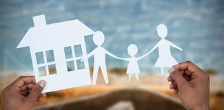 拿着与她的房子的手的综合图象一个家庭纸的 免版税库存照片
