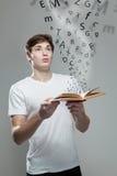 拿着与字母表信件的年轻人一本书 免版税库存照片